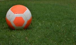 Трава оранжевого футбола футбола зеленая с экземпляр-космосом предпосылки игрока Стоковое Фото