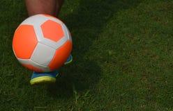 Трава оранжевого футбола футбола зеленая с экземпляр-космосом предпосылки игрока Стоковые Фото