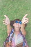 трава ослабляя Взгляд сверху красивой молодой женщины в солнечных очках и pareo лежа на зеленой траве в парке  Стоковая Фотография RF