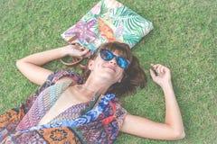 трава ослабляя Взгляд сверху красивой молодой женщины в солнечных очках и pareo лежа на зеленой траве с пляжем кладут в мешки вну Стоковые Изображения RF