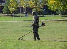 трава работника кося с щеткой бензина триммер Стоковая Фотография
