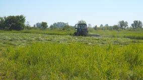 Трава трактора кося в луге видеоматериал