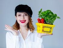 Травы женщины базилика и красные томаты в условный расчетный набор представительных потребительских товаров Стоковое Изображение