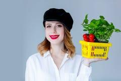 Травы женщины базилика и красные томаты в условный расчетный набор представительных потребительских товаров Стоковое Фото