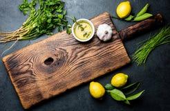 Травы - лук spreeng, лимоны, кориандр, розмариновое масло чеснока и масло вокруг деревянной разделочной доски, взгляд сверху, кос Стоковая Фотография
