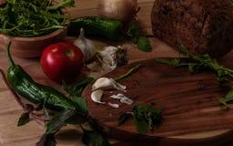 Травы, овощи и хлеб вокруг темной деревянной разделочной доски Стоковые Изображения RF