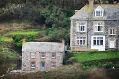 Травянистые холмы с домами на верхней части в гаван Исаак, Корнуолле, Англии стоковое изображение rf