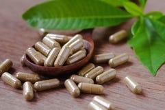 травяное лекарство в капсуле на деревянной таблице с зелеными листьями Стоковое фото RF