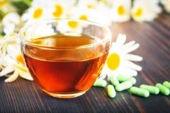 Травяной чай в прозрачной чашке, капсулах и стоцвете цветет на деревянном столе Концепция phytotherapy Стоковое Изображение RF