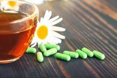 Травяной чай в прозрачной чашке, капсулах и стоцвете цветет на деревянном столе Концепция phytotherapy Стоковое Изображение
