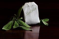 Травяной чай, листья salvia и пакетик чая, темная предпосылка Стоковая Фотография
