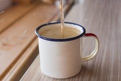 Травяной чай полит в покрытую эмалью кружку на деревянной предпосылке в кухне и падения чая летают Стоковые Фотографии RF