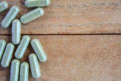 Травяные капсулы на древесине Стоковое Фото