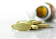 Травяные таблетки, медицина из бутылки пилюльки на белой предпосылке Стоковые Фотографии RF