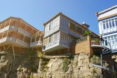 Традиционная грузинская архитектура стиля на скалах в городке Тбилиси старом Деревянные дома с красочными высекаенными балконами стоковые фото