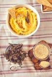 Традиционная закуска Hummus Ближнего Востока служила с травами, приправленными с в винтажной керамической плитой Взгляд сверху то стоковое изображение