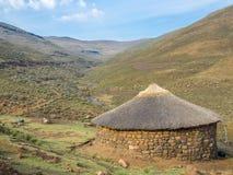 Традиционная покрыванная соломой каменная круглая хата Basutho в гористых местностях горы Лесото, Южной Африки Стоковое Изображение