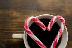 Традиционное горячее темное coffe с ручками конфеты на деревянной предпосылке Питье рождества деревянное украшений рождества экол стоковые фото