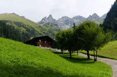 Традиционное шале в европейских горных вершинах на зеленом выгоне горы стоковые фотографии rf