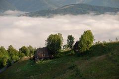 Традиционные дома в Трансильвании, восход солнца с туманом в горах, Румынией стоковые изображения rf