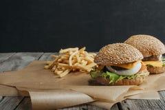 традиционные домодельные cheeseburgers на бумаге выпечки Стоковое Фото