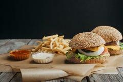 традиционные домодельные cheeseburgers на бумаге с французскими фраями, кетчуп выпечки Стоковые Изображения RF