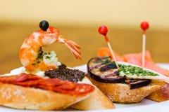 Традиционные испанские закуски кухни Канапе багета тап с сосисками chorizo, черными оливками, зажаренным баклажаном, семгой Стоковое Изображение