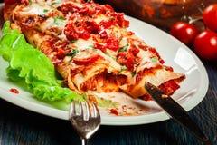 Традиционные мексиканские энчилада с мясом цыпленка, пряным томатным соусом и сыром на плите Стоковые Фото