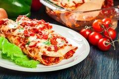 Традиционные мексиканские энчилада с мясом цыпленка, пряным томатным соусом и сыром на плите Стоковое фото RF