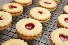 Традиционные печенья Linzer рождества с вареньем на охладительной решетке Стоковое Фото