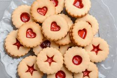 Традиционные печенья Linzer рождества с сладостным вареньем на плите Стоковое фото RF