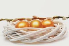 Традиционные яичка покрашенные в золотой венке цвета сплетенном внутренностью деревянном Стоковые Фото