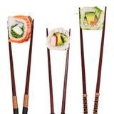 Традиционные японские части суш помещенные между отделенными палочками, на белой предпосылке Стоковые Фотографии RF