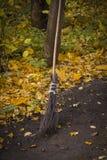 Традиционный веник ведьмы на хеллоуине с сухими листьями на том основании стоковые изображения rf