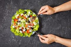 Традиционный греческий салат с свежими овощами, сыром фета и оливками на каменной предпосылке Женские нож и firk владением рук Стоковое Изображение