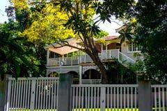 Традиционный дом Queenslander австралийца с тропическими листвой и древесиной и лестницами стоковые изображения