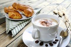 Традиционный итальянский завтрак с капучино и круассанами на деревенском деревянном столе Стоковое Изображение RF