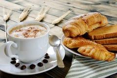 Традиционный итальянский завтрак с капучино и круассанами на деревенском деревянном столе Стоковые Фотографии RF