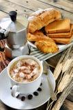 Традиционный итальянский завтрак с капучино и круассанами на деревенском деревянном столе Стоковое Фото