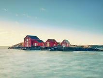 Традиционный красный цвет и Белые Дома в малом рыбацком поселке Молчаливый залив весной Норвегия стоковые фотографии rf