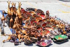 Традиционный местный африканский рынок сувенира на улице с строками высекаенной руки покрасил деревянные шары, жирафов, слонов с  стоковое изображение