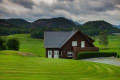 Традиционный норвежский деревянный дом стоя на лужайке и горах на заднем плане норвежец дома типичный типичный норвежец Стоковые Фотографии RF