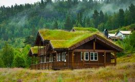 Традиционный норвежский деревянный дом стоя на лужайке и горах на заднем плане норвежец дома типичный типичный норвежец Стоковое фото RF