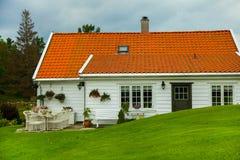Традиционный норвежский деревянный дом стоя на лужайке и горах на заднем плане норвежец дома типичный типичный норвежец Стоковое Изображение