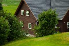 Традиционный норвежский деревянный дом стоя на лужайке и горах на заднем плане норвежец дома типичный типичный норвежец Стоковые Фото