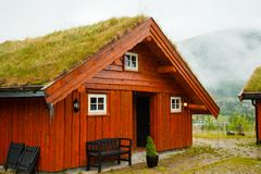 Традиционный норвежский деревянный дом стоя на лужайке и горах на заднем плане норвежец дома типичный типичный норвежец Стоковые Изображения