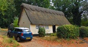 Традиционный покрыванный соломой коттедж при мини автомобиль припаркованный снаружи стоковое фото rf