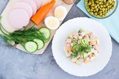 Традиционный русский салат более olivier и ингридиенты для своей подготовки стоковая фотография