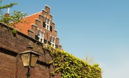 Традиционный старый голландский дом с крышей лестницы и плитками апельсина Стоковая Фотография