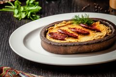 Традиционный турецкий, арабская кухня Hummus с сосиской салями, в плите глины, на деревянной таблице На белой плите стоковые изображения rf